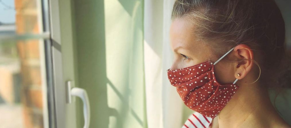 woman in mask looking out the window